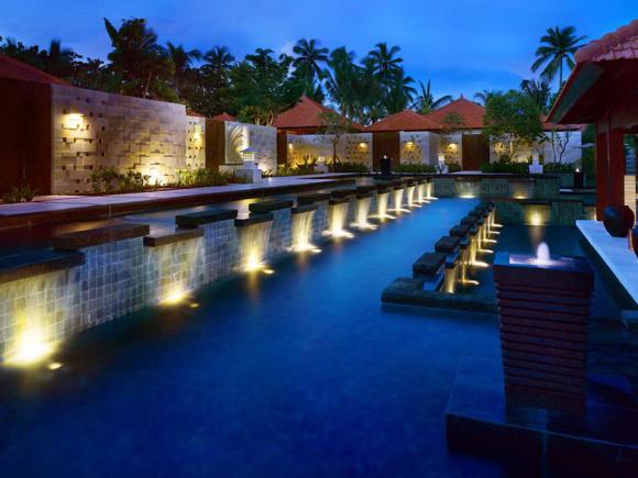 酒店介绍: 1991年开业,2007年装修,共有636间房 Grand Hyatt Bali(巴厘岛君悦酒店),位于努沙杜瓦,这里是巴厘岛知名的旅游度假圣地。酒店离沙努尔、库塔和登巴萨城都很近,出行十分便利。酒店周边环境优美,在湖泊、花园和六个游泳池的围绕下,这座巴厘岛风格的建筑可以说是一座水上宫殿,极富自然美和现代美。 豪华的酒店宽敞明亮,在自然美景的映衬下格外美丽,在夜晚灯光的环绕中又具有另一种美感。客房包括豪华海滨别墅、豪华套间、海景房等,巴厘风格的建筑和装饰品可在房内随处见到,比如传统石雕作品和本